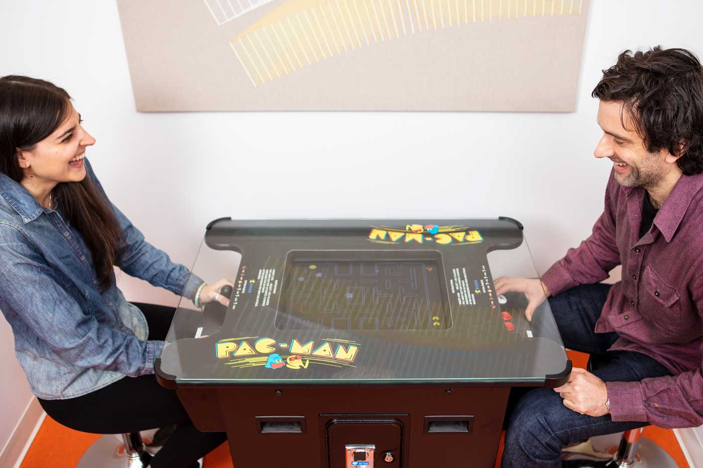 Two colleagues playing PacMan and laughing together.