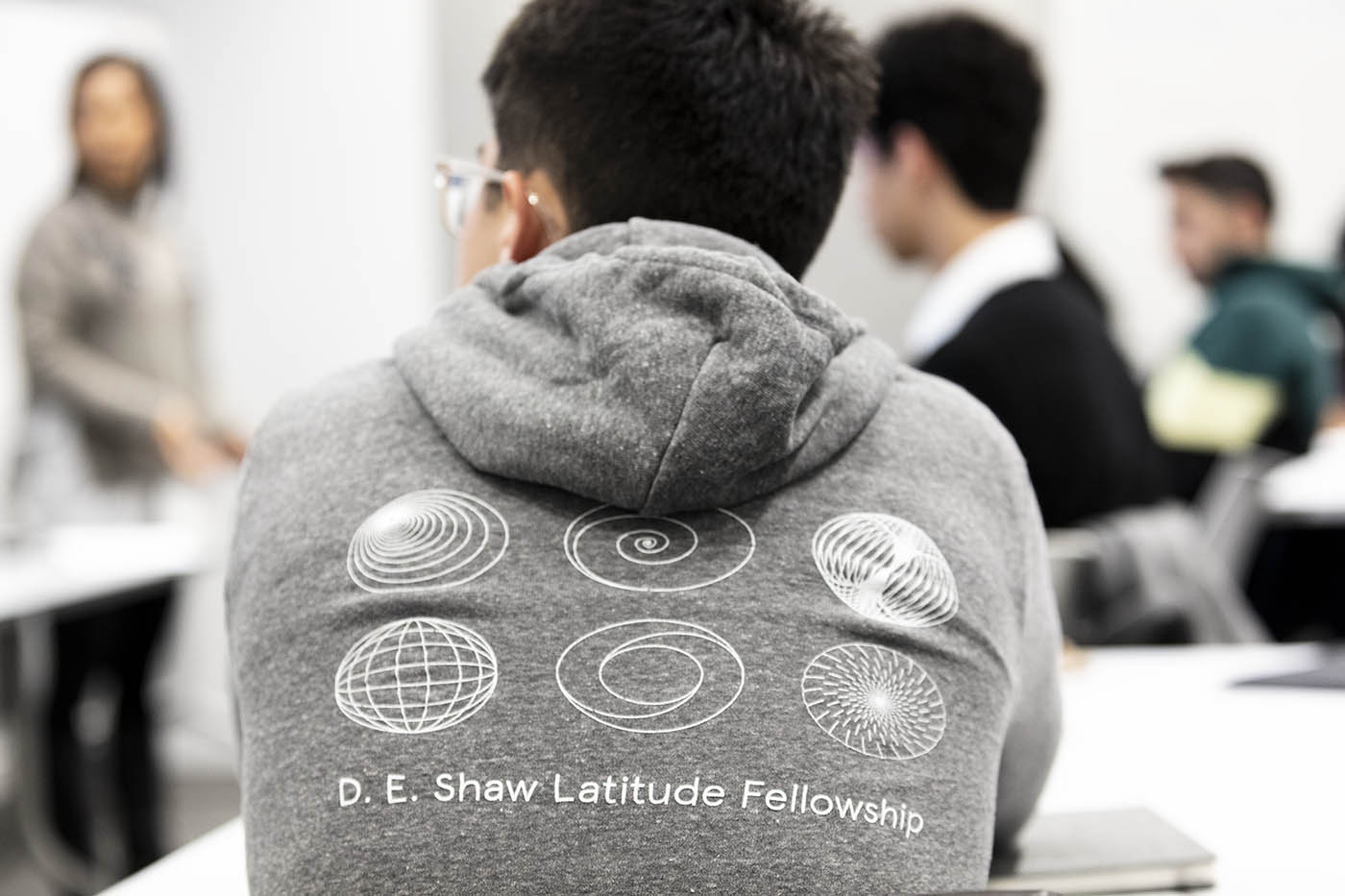Employee wears a D. E. Shaw Latitude Fellowship sweatshirt.