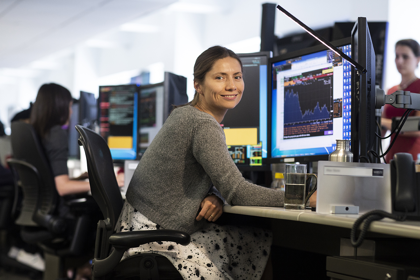 Woman sitting at her workstation smiling at the camera on the trading floor.