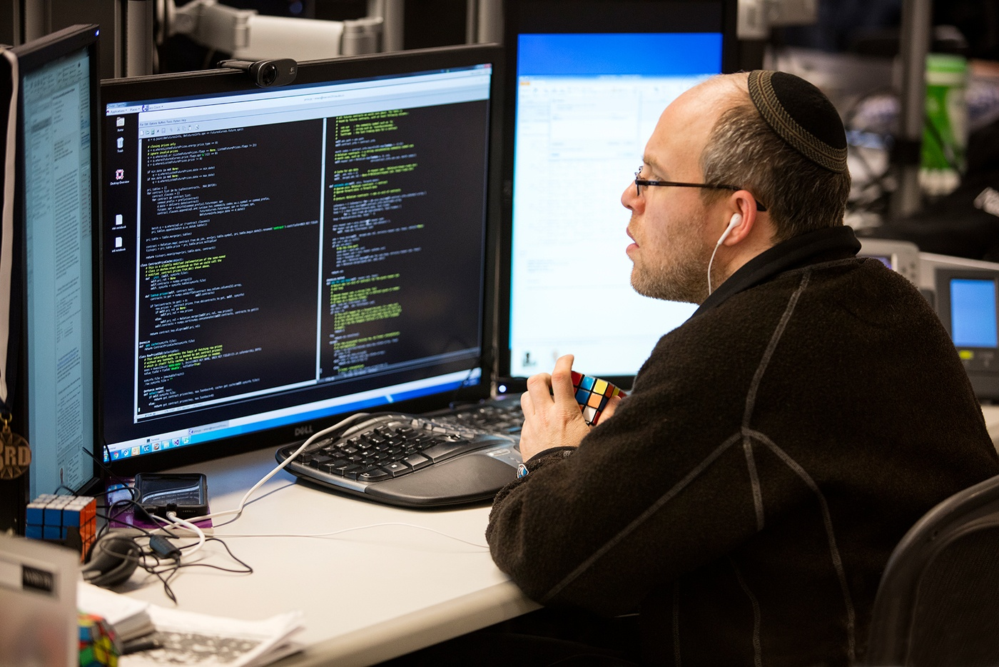 Man wearing kippah and headphones looks at code at his workstation while playing with Rubick's Cubes.